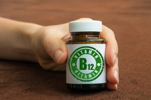 Human hand holding a bottle of pills with vitamin B12 on brown background